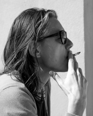 Portret van vrouw die nog geniet van een sigaret.