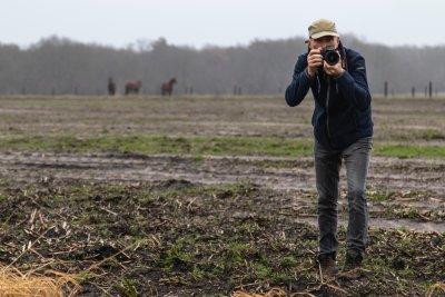 Landschapsfotograaf aan het werk op de Uffelter Es met toekijkende paarden.