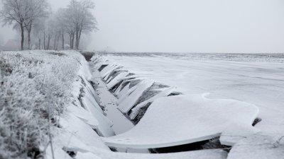 Gebroken ijsplaten boven een sloot langs een akker in de winter bij Ravenswoud in Friesland.
