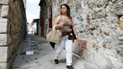 Vrouw met boodschappentas in straatje in Palermo op Sicilië in Italië.