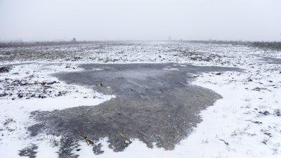 Bevroren plas op besneeuwde akker bij Ruinerwold in Drenthe.