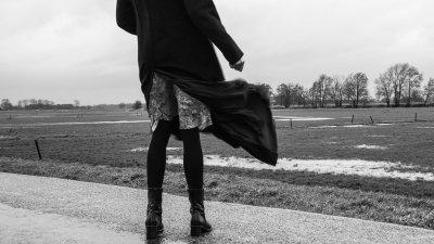 De wind laat de mantel van een wandelende dame wapperen in het Hollandse platteland.
