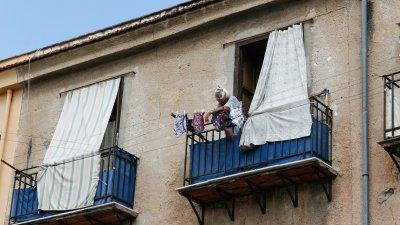 Oude vrouw op balkon met wasgoed in Palermo op Sicilië in Italië.