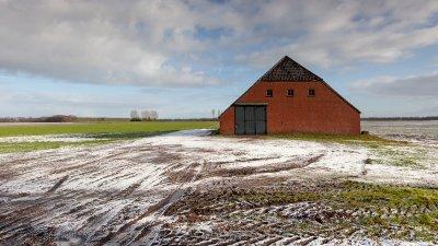 Karakteristieke schuur van rode bakstenen met beetje sneeuw in Oost Groningen.