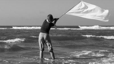 Vrouw met witte vlag in de Noordzee in het kader van het White flags project.
