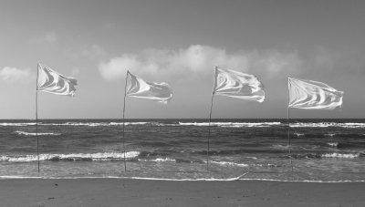 Witte vlaggen wapperen boven de kust van de Noordzee.