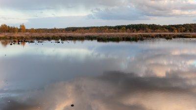 Stille waterenweerspiegelen wolken boven het Dwingelderveld in Drenthe.