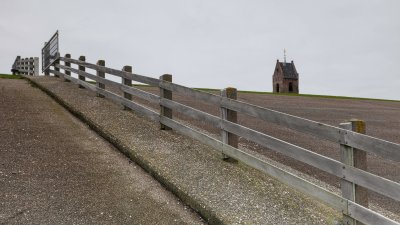 Kerktoren van Wierum achter de Zeedijk langs de Waddenkust in het Noorden van Friesland.