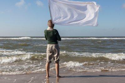 Vrouw mwt witte vlag langs de vloedlijn van het Noordzee strand.
