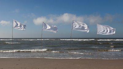 Wapperende witte vlaggen langs de vloedlijn aan het Noordzee strand.
