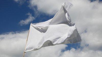 Witte vlag wapperend in de wind op Hollandse zomerdag.