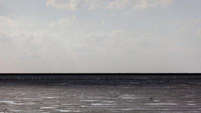 Donkere schaduw van een wolk trekt over het drooggevallen Uithuizerwad langs de Groningse waddenkust.